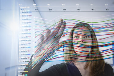 Businesswoman inspecting graph on interactive display - CUF37670