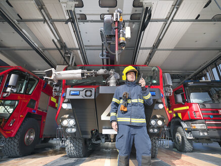 Fireman using walkie talkie in front of fire engines in airport fire station - CUF37691
