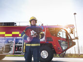 Portrait of fireman in front of fire engine in airport fire station - CUF37694