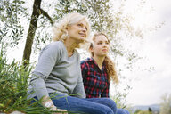 Mother and teenage daughter sitting on grass - CUF37703