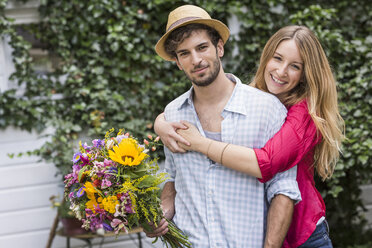 Portrait of young couple with bunch of flowers hugging in garden - CUF37730