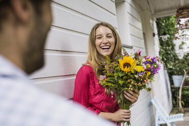 Young woman with bunch of flowers in front porch - CUF37733