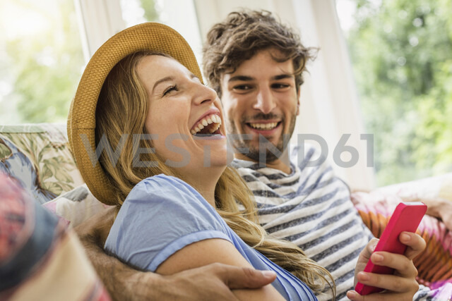Young couple texting on smartphone in living room - CUF37736