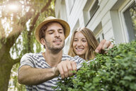 Young couple pruning bush outside house - CUF37745