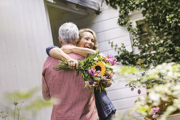 Wife holding bunch of flowers and hugging husband - CUF37748