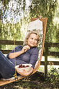 Mature woman relaxing with bowl of cherries on hammock - CUF37760