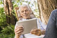 Mature man using digital tablet on hammock - CUF37766