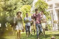 Friends walking in garden with picnic - CUF37769