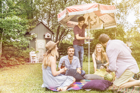 Friends having picnic in garden - CUF37790