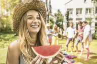 Woman wearing straw hat eating watermelon - CUF37799