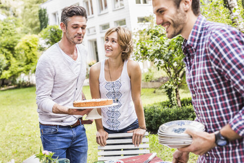 Group of friends setting up garden party, mid adult man carrying cake - CUF37805
