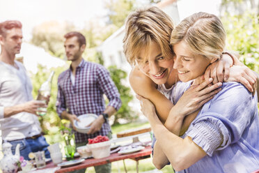 Group of friends setting up garden party, two female friends embracing - CUF37811