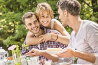 Group of friends enjoying garden party, young woman hugging young man - CUF37826