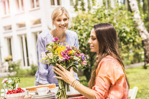 Two female friends in garden, looking at bunch of flowers - CUF37832