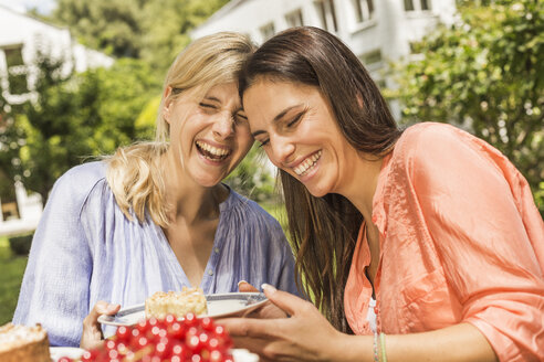 Two female friends in garden, laughing, holding plate with dessert - CUF37835