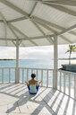 Young woman practicing yoga lotus pose in coastal gazebo, Providenciales, Turks and Caicos Islands, Caribbean - ISF14668