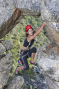Young female rock climber climbing up rock face - ISF14745