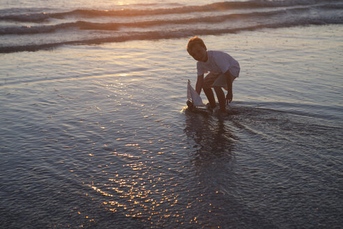 Boy playing toy boat on beach - ISF14775
