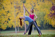 Yoga instructor teaching young woman in forest - ISF14799