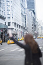 Young woman hailing a yellow cab, New York, USA - ISF14877