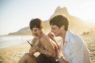 Young couple listening to music, Ipanema Beach, Rio, Brazil - ISF14916