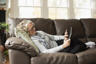 Senior woman relaxing on sofa with digital tablet - ISF14937