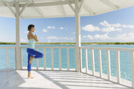 Young woman doing yoga in coastal gazebo, Providenciales, Turks and Caicos Islands, Caribbean - ISF15084