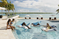 Group of young adults relaxing in swimming pool, Providenciales, Turks and Caicos Islands, Caribbean - ISF15087