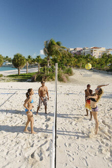 Four young adult friends playing beach volleyball, Providenciales, Turks and Caicos Islands, Caribbean - ISF15090