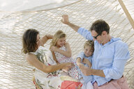 Family relaxing in beach hammock, Providenciales, Turks and Caicos Islands, Caribbean - ISF15105