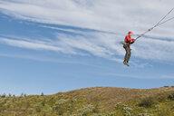 Teenage boy swinging on rope swing - CUF37906