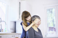 Girl covering grandmothers eyes at kitchen table - CUF37930