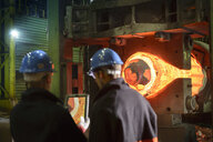 Steelworkers using digital tablet with 10,000 tonne forging press in steelworks - CUF37948
