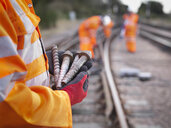 Railway maintenance worker holding track screws, close up - CUF37987