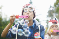 Siblings blowing bubbles in garden - CUF38029