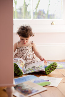 Female toddler reading storybooks in bedroom - ISF15312