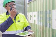 Worker with tablet wearing safety vest using walkie talkie at container - ZEF15741
