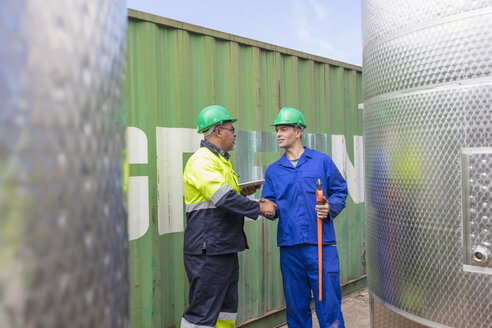 Two workers at container shaking hands - ZEF15744