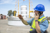 Man in workwear on construction site talking on cell phone - ZEF15750