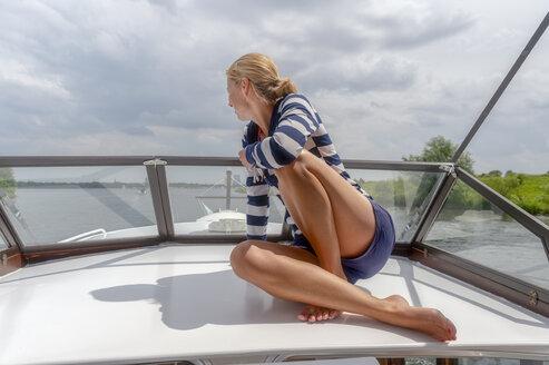 Netherlands, Limburg, Osen, Meuse river, woman sitting on upper deck of a sailing yacht - FRF00688
