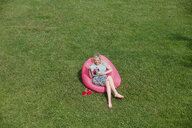 Woman sitting in inflatable seat on meadow looking at photo book - RHF02033