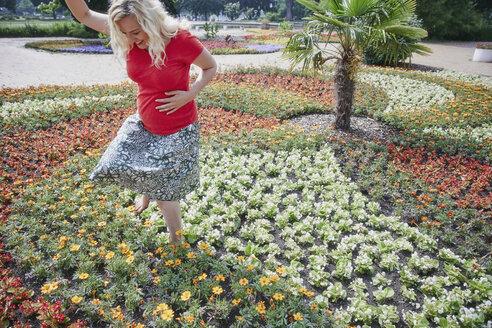 Happy pregnant woman walking through blooming flowers in park - RHF02054