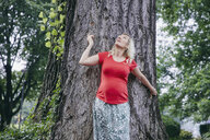 Smiling pregnant woman standing at a tree in park looking up - RHF02060