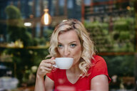 Portrait of blond woman drinking coffee in a cafe - RHF02069