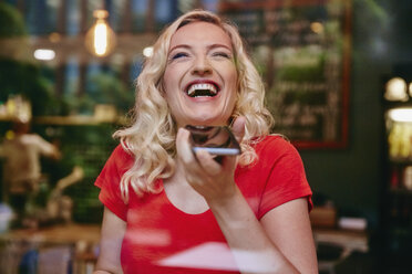 Portrait of laughing blond woman using smartphone in a cafe - RHF02072