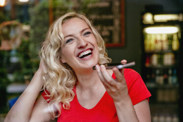 Portrait of laughing blond woman using smartphone in a cafe - RHF02075