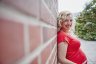 Portrait of smiling pregnant woman outdoors leaning against a brick wall - RHF02078