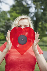 Woman holding a heart-shaped vinyl record outdoors - RHF02087