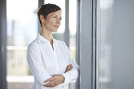 Businesswoman in office looking out of window - RBF06356
