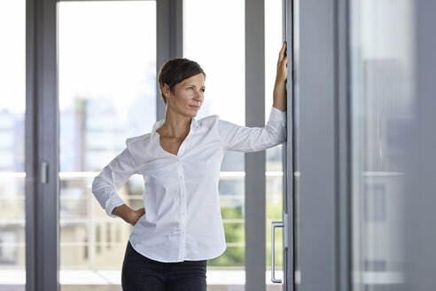 Businesswoman standing in office looking out of window - RBF06365